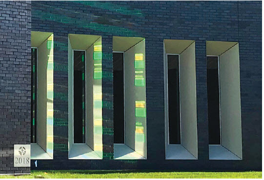 Viewed from a northern perspective, a colorful reflection from the dichroic glass on the west elevation is displayed over brick and more vividly onto the GFRC.