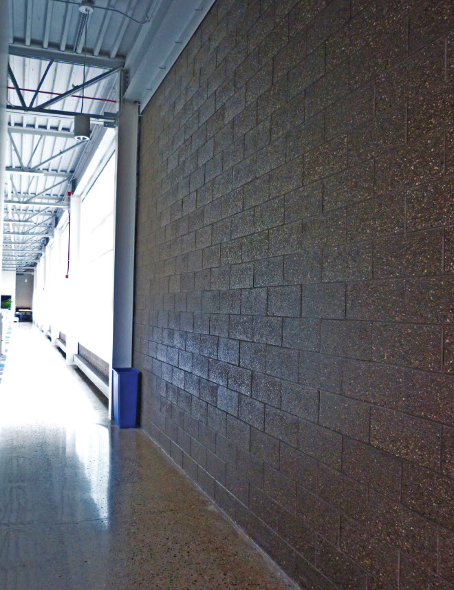 Shear wall of burnished charcoal CMU with contrasting aggregate adds distinctive aesthetic and provides lateral support. 94X Iron Black mortar joints add to the dramatic effect of the executive conference room and perimeter walls.