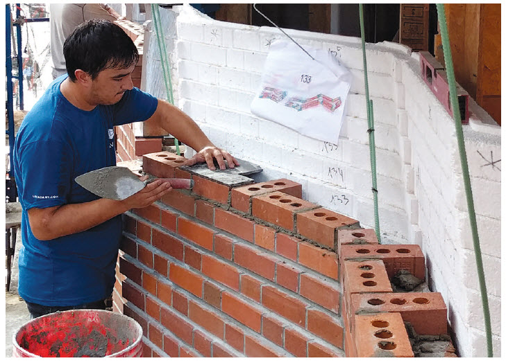 Brick masons at work on the exterior façade, setting sections of brick one course at a time with offset tools and brick course reference drawings. Brick course drawings produced by the architect have color-coded brick sizes to further streamline construction. Underside of the balcony floor structure projects through the brick facade at each floor level.