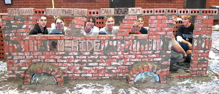 Students pose by their bricklaying project – a depiction of the college's CyRide transit system bus.