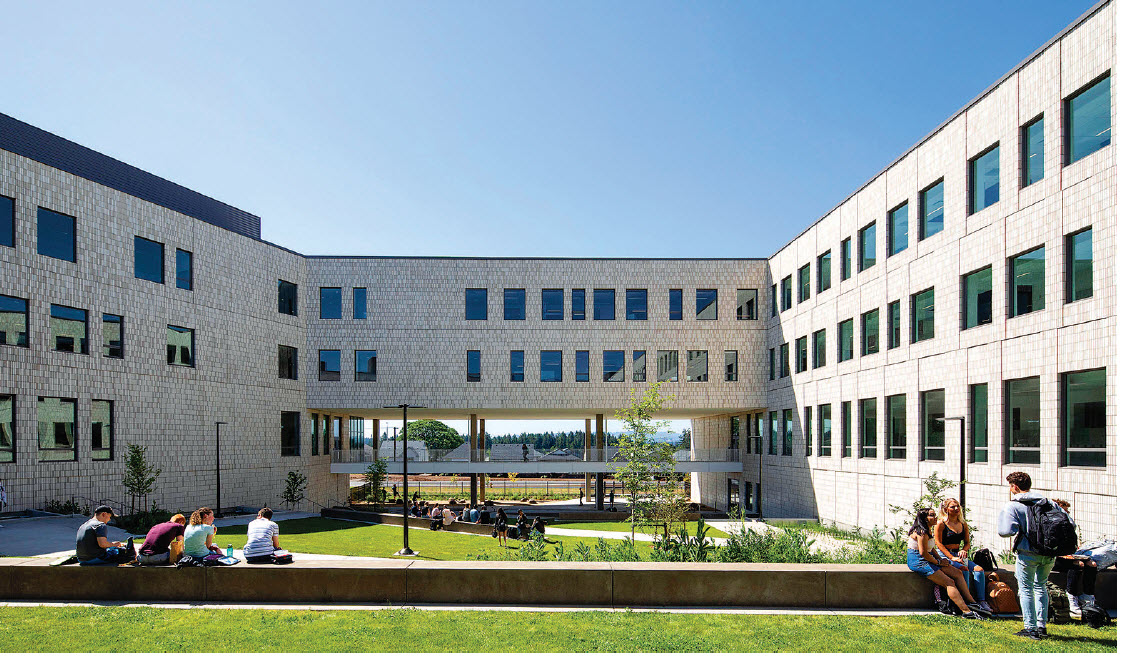 Soldier coursing of Norman Mutual Materials glazed and unglazed white veneer brick reflect sunlight throughout spacious trapezoidal courtyard, alcoves and interior glassed commons.