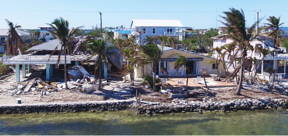 A demolished wood frame home on stilts sits next to an undamaged masonry home on the eastern edge of Florida's Ramrod Key after 2017's Hurricane Irma.